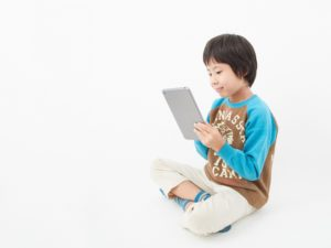タブレット画面を見る子どもの写真